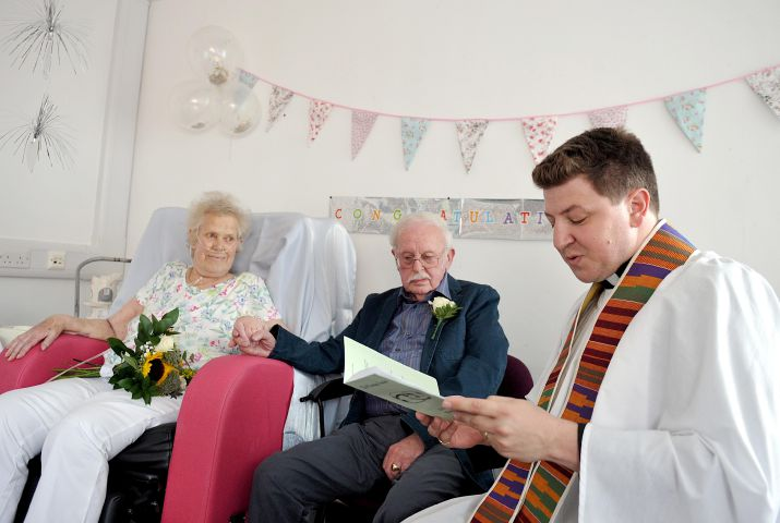 FGH WEDDING --- Val Squire got to marry her partner of 31 years Brian Squire, both from Grange, during a special ceremony conducted by Chaplain Ed Northey on Ward 9 at Furness General Hospital. Val has been told she has just days to live, and so the couple decided to make their vows to one another. // Pictured: Val and Brian join hands during the ceremony, with Chaplain Ed Northey (right) Thursday 9th June 2016 LINDSEY DICKINGS